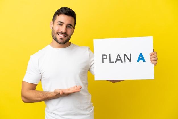 Młody przystojny kaukaski mężczyzna odizolowany na żółtym tle trzymający tabliczkę z komunikatem plan a i wskazujący go