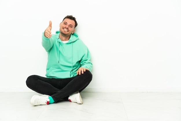 Młody przystojny kaukaski mężczyzna siedzi na podłodze, ściskając ręce