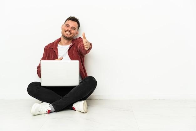 Młody przystojny kaukaski mężczyzna siedzi na podłodze z laptopem, ściskając ręce za zamknięcie dobrej oferty