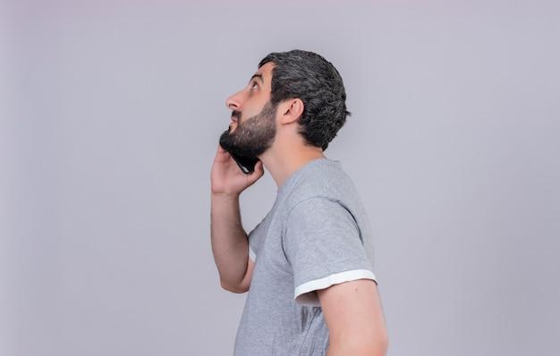 Młody przystojny kaukaski mężczyzna stojący w widoku profilu patrząc i rozmawia przez telefon na białym tle na białym tle z miejsca na kopię