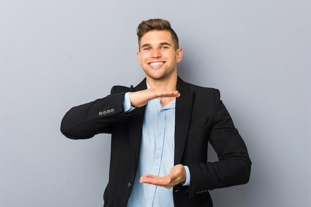 Młody przystojny kaukaski mężczyzna trzyma coś obiema rękami, prezentacja produktu.