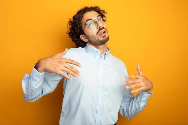 Młody przystojny kaukaski mężczyzna w okularach patrząc na kamery, trzymając ręce w powietrzu, wyjaśniając coś na białym tle na pomarańczowym tle