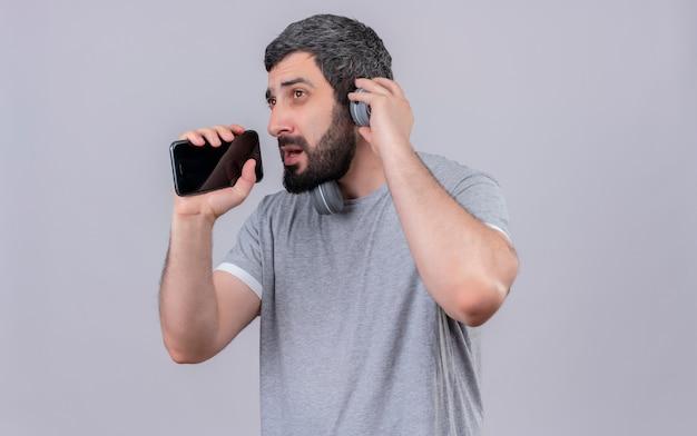 Młody przystojny kaukaski mężczyzna w słuchawkach udaje, że śpiewa i używa swojego telefonu komórkowego jako mikrofonu i patrzy w bok ręką na słuchawkach na białym tle z miejsca na kopię
