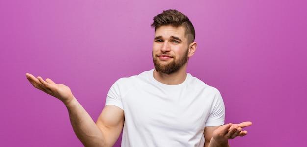 Młody przystojny kaukaski mężczyzna wątpi między dwiema opcjami.
