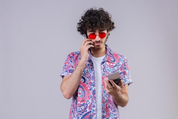 Młody przystojny kędzierzawy podróżnik mężczyzna w okularach przeciwsłonecznych rozmawia przez telefon, trzymając bilety lotnicze i portfel i patrząc na nich na odizolowanej białej ścianie z miejscem na kopię
