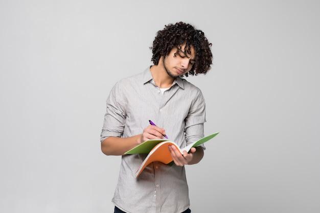 Młody przystojny kędzierzawy studencki mężczyzna z notatnikami nad odosobnionym na biel ścianie