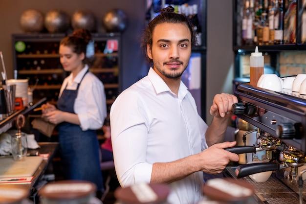 Młody przystojny kelner w białej koszuli przygotowuje świeże cappuccino przez ekspres do kawy, podczas gdy jego kolega wyciera szkło w miejscu pracy