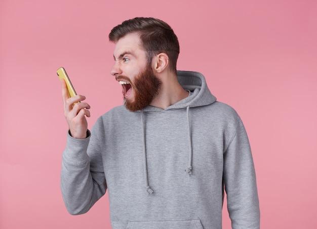 Młody przystojny kremujący zszokowany rudy brodaty mężczyzna w szarej bluzie, wygląda złowrogo i niezadowolony, kłóci się ze swoją dziewczyną przez telefon, stoi na różowym tle.