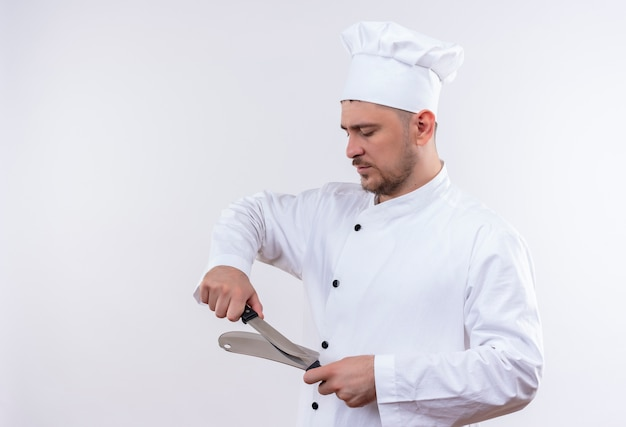 Młody przystojny kucharz w mundurze szefa kuchni do tarcia nóż i tasak na białym tle