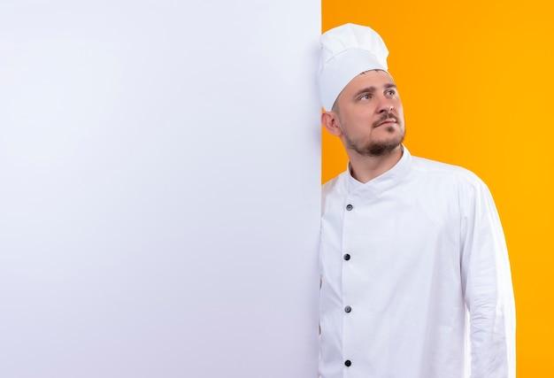 Młody przystojny kucharz w mundurze szefa kuchni stojący za białą ścianą, patrząc prosto na białym tle na pomarańczowej przestrzeni