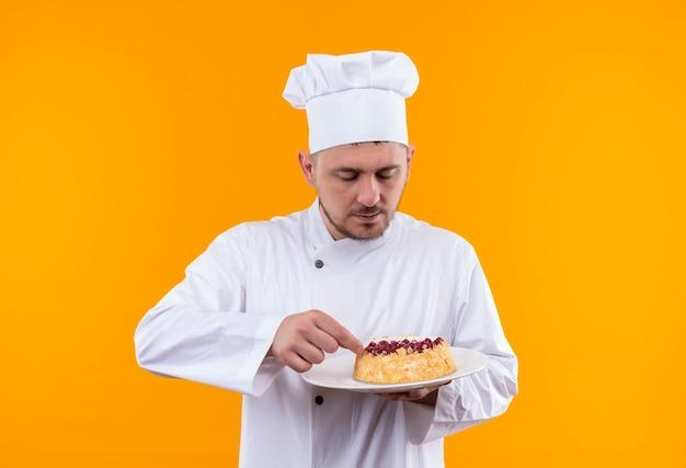 Młody przystojny kucharz w mundurze szefa kuchni, trzymając i patrząc na talerz ciasta na białym tle na pomarańczowej przestrzeni