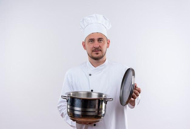 Młody przystojny kucharz w mundurze szefa kuchni, trzymając kocioł i jego okładkę, patrząc na pojedyncze białe miejsce