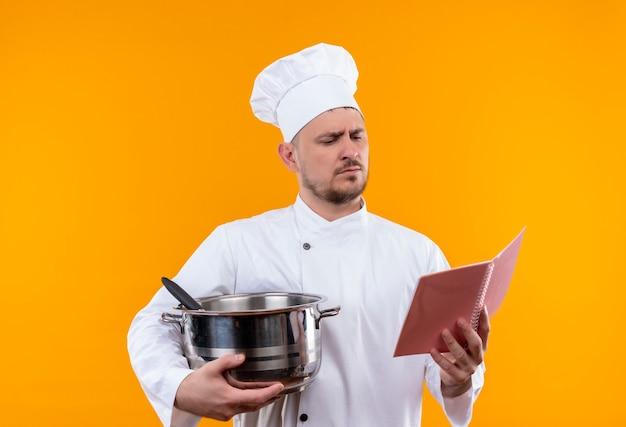 Młody przystojny kucharz w mundurze szefa kuchni trzymając kocioł i notes i patrząc na notes na odizolowanym pomarańczowym obszarze