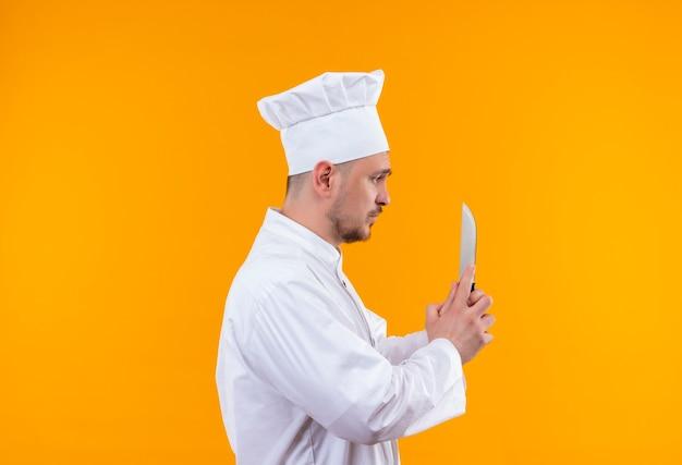 Młody przystojny kucharz w mundurze szefa kuchni trzymając nóż patrząc na to stojąc w widoku profilu na odizolowanej przestrzeni pomarańczowy