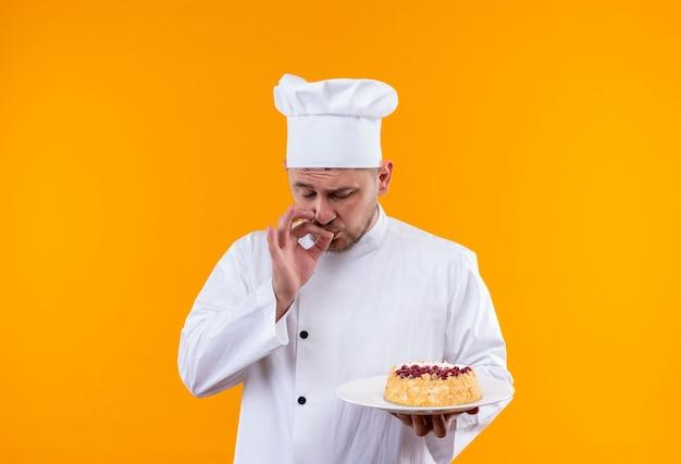 Młody przystojny kucharz w mundurze szefa kuchni, trzymając talerz ciasta i robi smaczny gest na białym tle na pomarańczowej przestrzeni