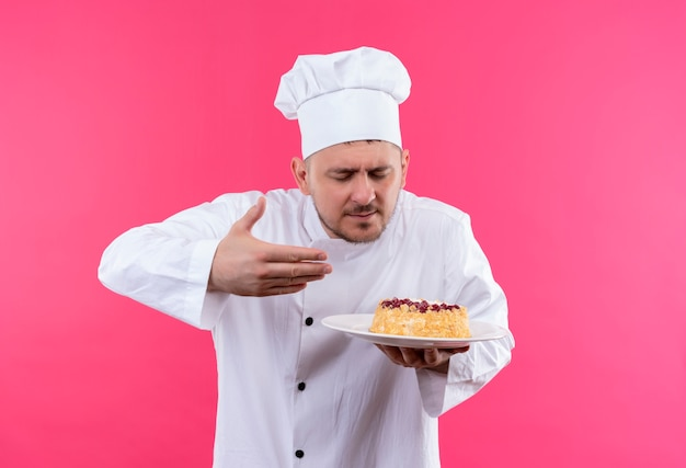 Młody przystojny kucharz w mundurze szefa kuchni, trzymając talerz ciasta i wąchając go na białym tle na różowej przestrzeni