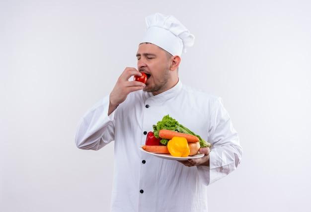 Młody przystojny kucharz w mundurze szefa kuchni trzymając talerz z warzywami i gryzącym pomidorem z zamkniętymi oczami na odosobnionej białej przestrzeni