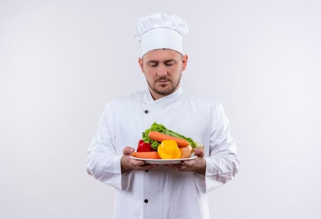Młody przystojny kucharz w mundurze szefa kuchni trzymając talerz z warzywami i patrząc na nich na na białym tle
