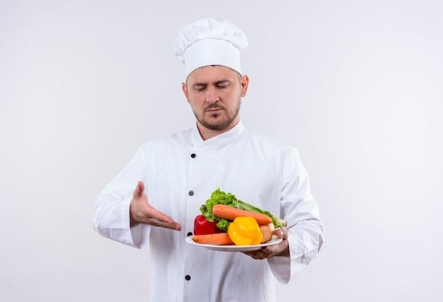 Młody przystojny kucharz w mundurze szefa kuchni trzymając talerz z warzywami, patrząc i wskazując na nich na na białym tle