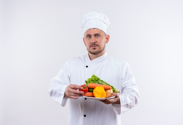 Młody przystojny kucharz w mundurze szefa kuchni trzymając talerz z warzywami, patrząc na pojedyncze białe miejsce