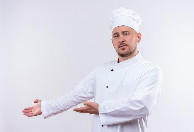 Młody przystojny kucharz w mundurze szefa kuchni, wskazując rękami na boku, patrząc na białym tle na białej przestrzeni