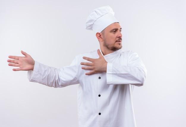 Młody przystojny kucharz w mundurze szefa kuchni, wskazując rękami po lewej stronie i patrząc na bok na na białym tle