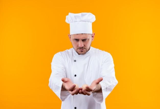 Młody przystojny kucharz w mundurze szefa kuchni wyciągając się i pokazując puste ręce i patrząc na nie odizolowane na pomarańczowej przestrzeni