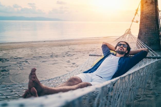 Młody przystojny łaciński mężczyzna relaksuje w hamaku na plaży przy zmierzchem na plaży w okularach przeciwsłonecznych.