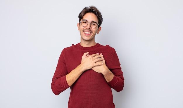 Młody przystojny latynoski mężczyzna czuje się romantyczny, szczęśliwy i zakochany, uśmiechając się radośnie i trzymając ręce blisko serca