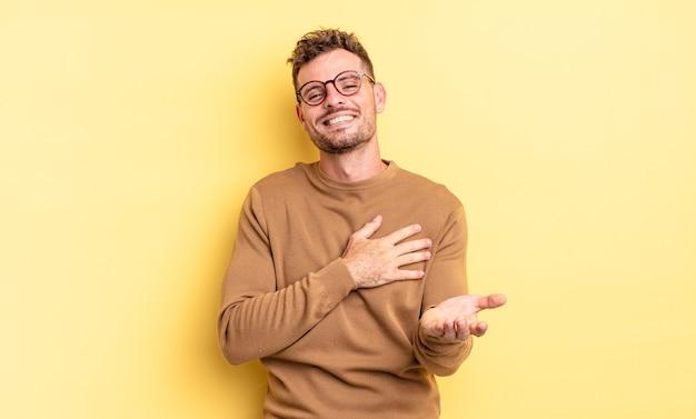 Młody przystojny latynoski mężczyzna czuje się szczęśliwy i zakochany, uśmiechając się jedną ręką przy sercu, a drugą wyciągniętą do przodu