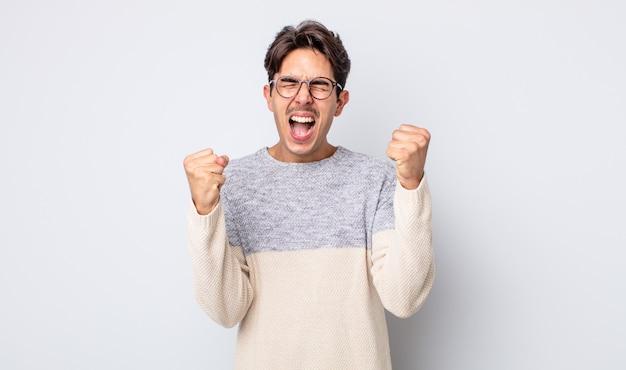 Młody przystojny latynoski mężczyzna czuje się szczęśliwy, pozytywny i odnosi sukcesy, świętuje zwycięstwo, osiągnięcia lub szczęście