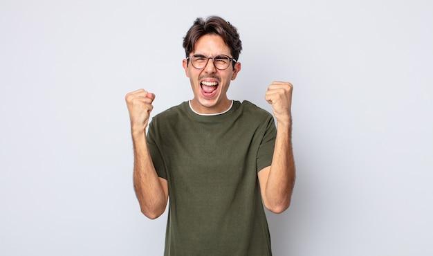 Młody przystojny latynoski mężczyzna czuje się szczęśliwy, zaskoczony i dumny, krzyczy i świętuje sukces z dużym uśmiechem