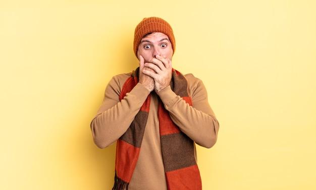 """Młody przystojny latynoski mężczyzna zakrywający usta dłońmi ze zszokowanym, zaskoczonym wyrazem twarzy, zachowujący tajemnicę lub mówiący """"ups"""""""