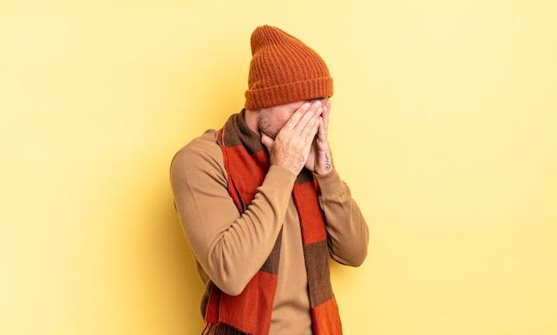 Młody przystojny latynoski mężczyzna zasłaniający oczy dłońmi ze smutnym, sfrustrowanym wyrazem rozpaczy, płaczu, widok z boku