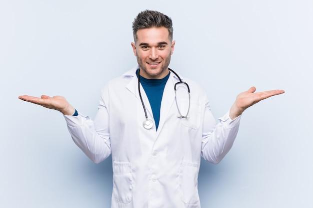 Młody przystojny lekarz mężczyzna sprawia, że skala z rękami, czuje się szczęśliwy i pewny siebie.
