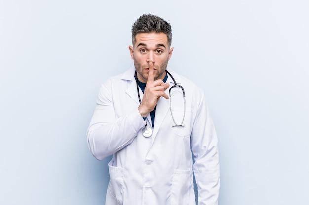 Młody przystojny lekarz mężczyzna trzyma sekret lub prosi o ciszę.