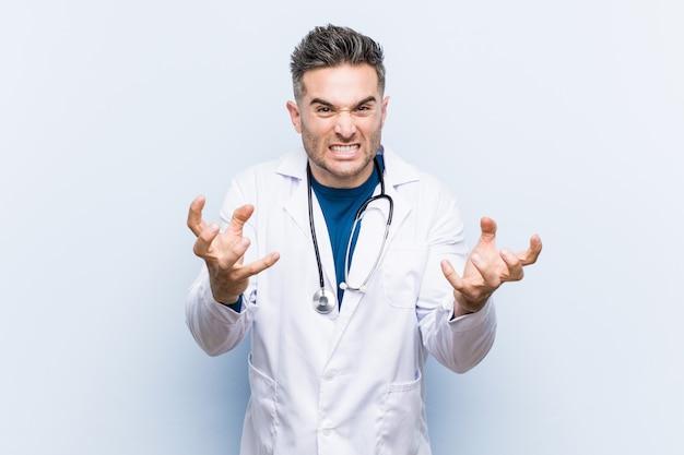 Młody przystojny lekarz mężczyzna zdenerwowany krzyczy z napiętymi rękami.