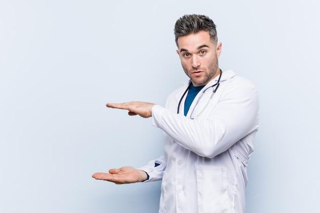 Młody przystojny lekarz mężczyzna zszokowany i zaskoczony, trzymając kopię miejsca między rękami.