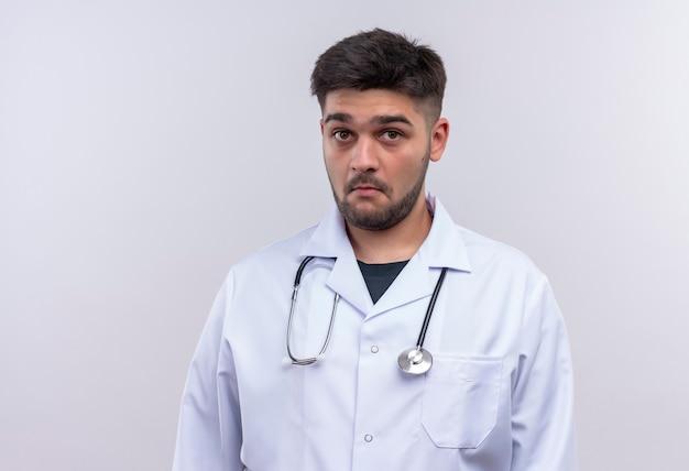 Młody przystojny lekarz ubrany w białą fartuch medyczny i stetoskop patrząc zaskoczony stojąc nad białą ścianą