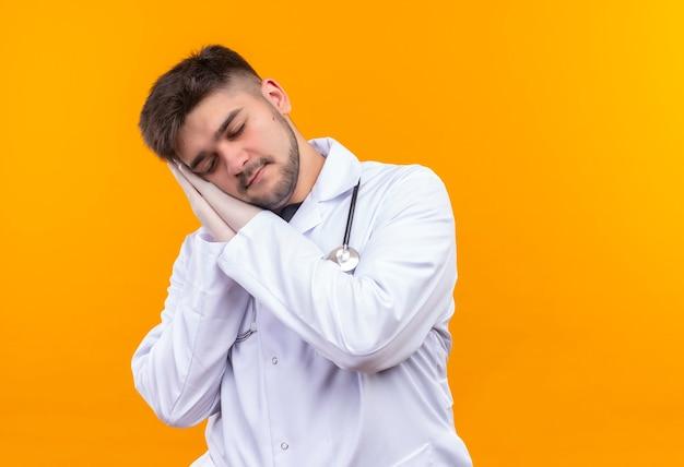 Młody przystojny lekarz ubrany w białą suknię medyczną białe rękawiczki medyczne i stetoskop do spania stojący nad pomarańczową ścianą