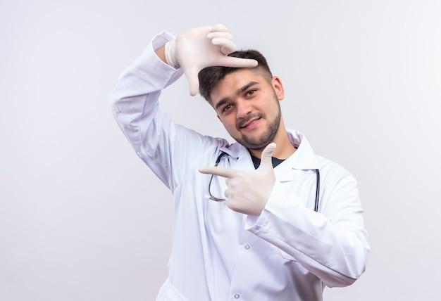 Młody przystojny lekarz ubrany w białą suknię medyczną białe rękawiczki medyczne i stetoskop łapie ramkę stojącą nad białą ścianą