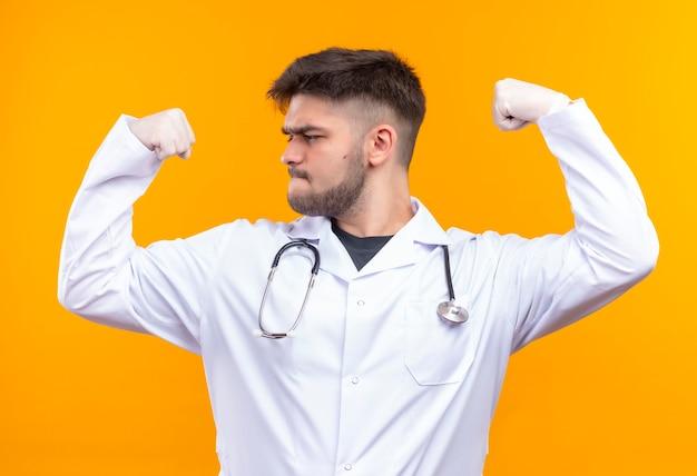 Młody przystojny lekarz ubrany w białą suknię medyczną białe rękawiczki medyczne i stetoskop mocno pokazujący swoją moc z podniesionymi pięściami stojącymi nad pomarańczową ścianą