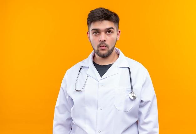Młody przystojny lekarz ubrany w białą suknię medyczną białe rękawiczki medyczne i stetoskop patrząc w zamyśleniu stojący nad pomarańczową ścianą
