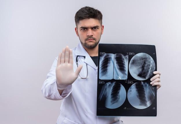 Młody przystojny lekarz ubrany w białą suknię medyczną białe rękawiczki medyczne i stetoskop pokazujący znak stopu trzymając tomografię stojącą nad białą ścianą