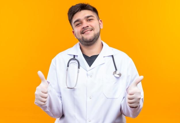 Młody przystojny lekarz ubrany w białą suknię medyczną białe rękawiczki medyczne i stetoskop robi szczęśliwe kciuki stojąc nad pomarańczową ścianą
