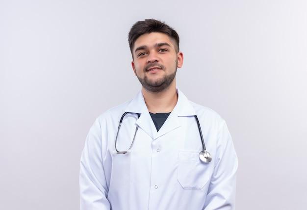 Młody przystojny lekarz ubrany w białą suknię medyczną białe rękawiczki medyczne i stetoskop uśmiechnięty stojący nad białą ścianą