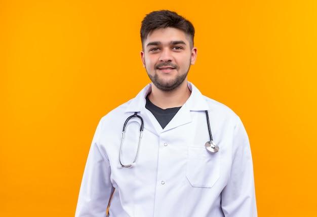 Młody przystojny lekarz ubrany w białą suknię medyczną białe rękawiczki medyczne i stetoskop uśmiechnięty stojący nad pomarańczową ścianą