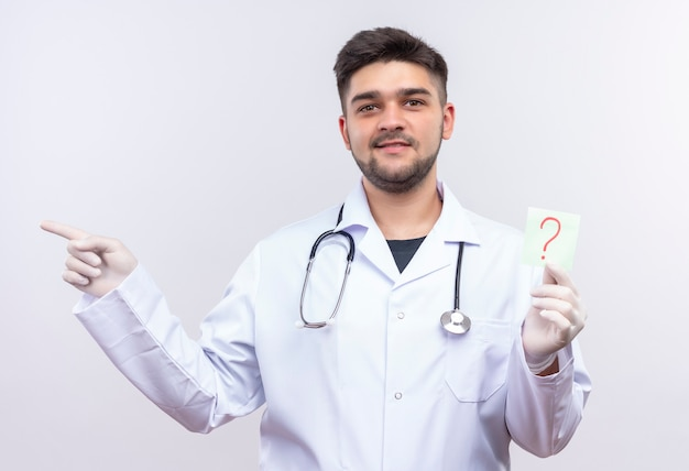 Młody przystojny lekarz ubrany w białą suknię medyczną białe rękawiczki medyczne i stetoskop uśmiechnięty, trzymając znak zapytania i wskazujący na prawo stojącego nad białą ścianą
