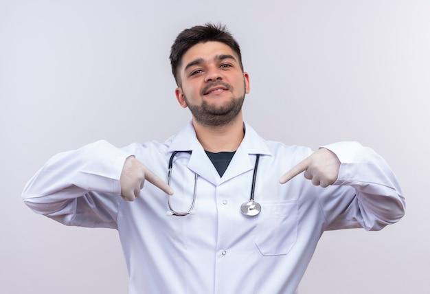 Młody przystojny lekarz ubrany w białą suknię medyczną białe rękawiczki medyczne i stetoskop, wskazując na siebie