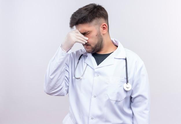 Młody przystojny lekarz ubrany w białą suknię medyczną białe rękawiczki medyczne i stetoskop zamykający katar stojący nad białą ścianą